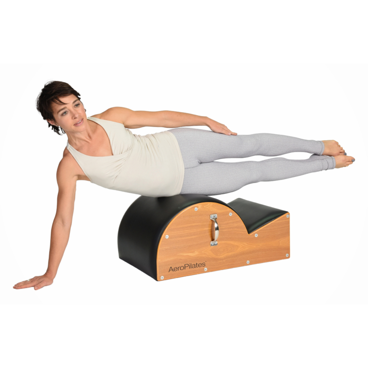 Woman workout on Aeropilates Spine Corrector Barrel