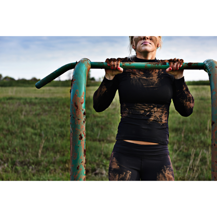 Muddy woman workout on Stamina Outdoor Fitness Power Tower