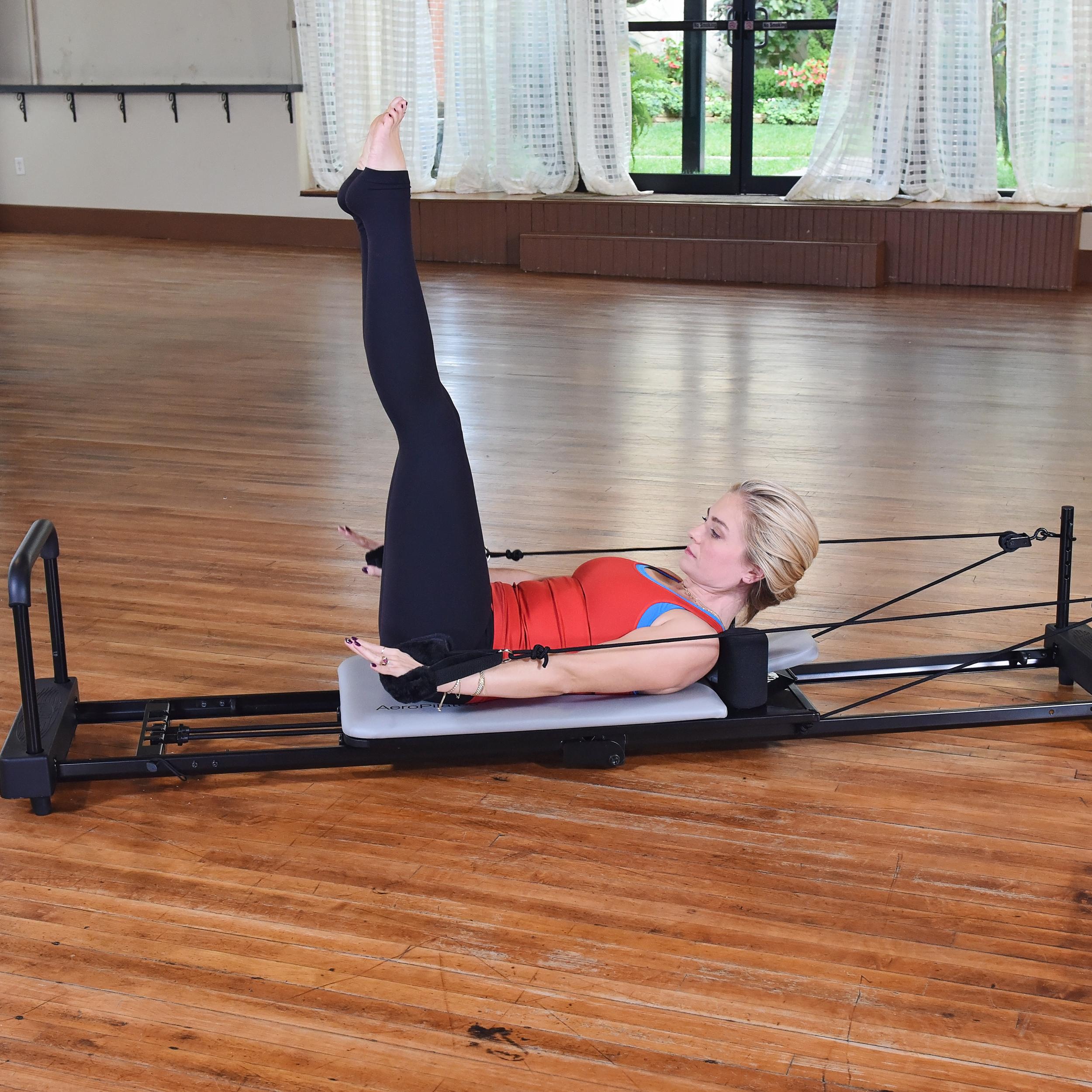 Woman performing on Aeropilates workout bundle.