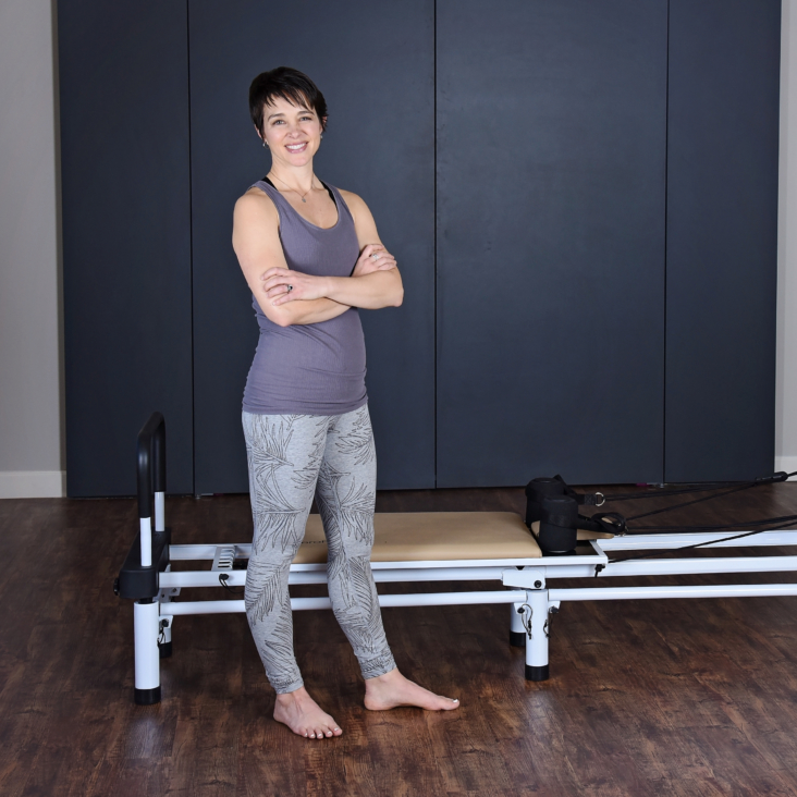 Woman standing in front of Full Body AeroPilates Workout.