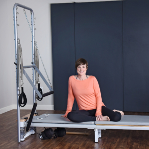 Woman seated on top of the pilates.