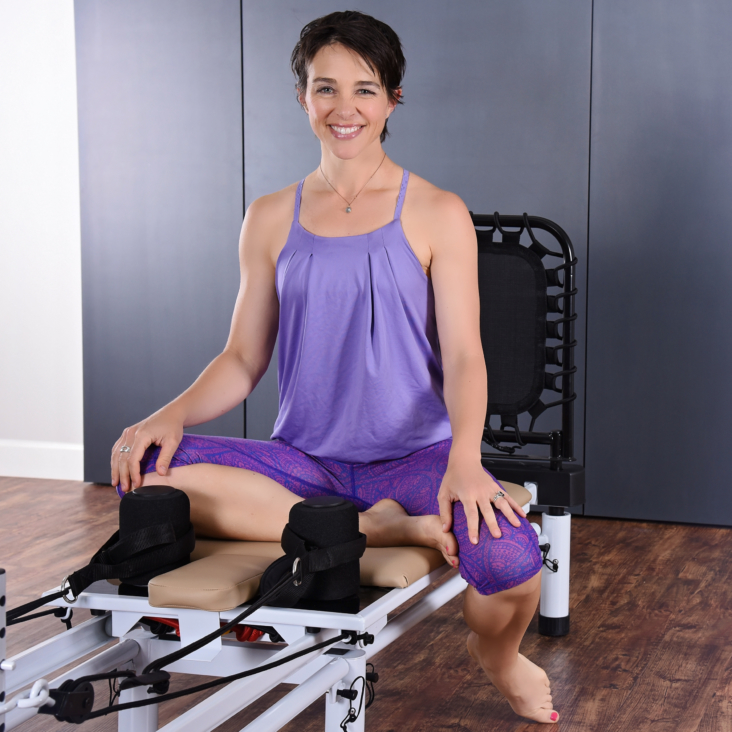 Woman smiling and seated on the pilates.
