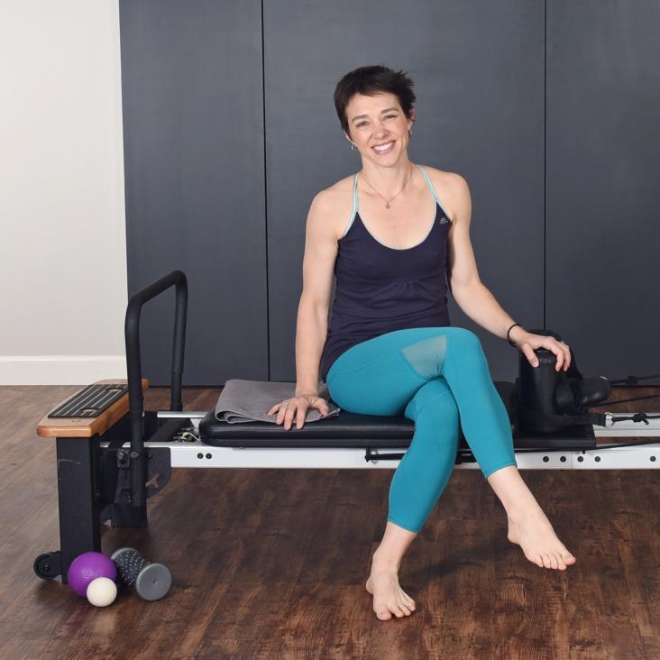 Woman seated smile on pilates.