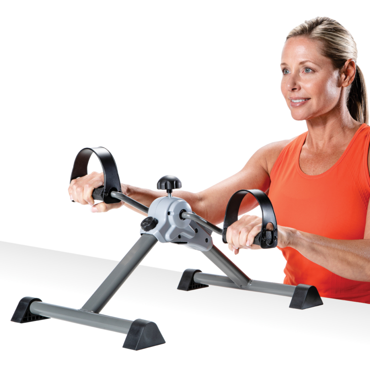 Seated woman pedaling an upper body cycle machine