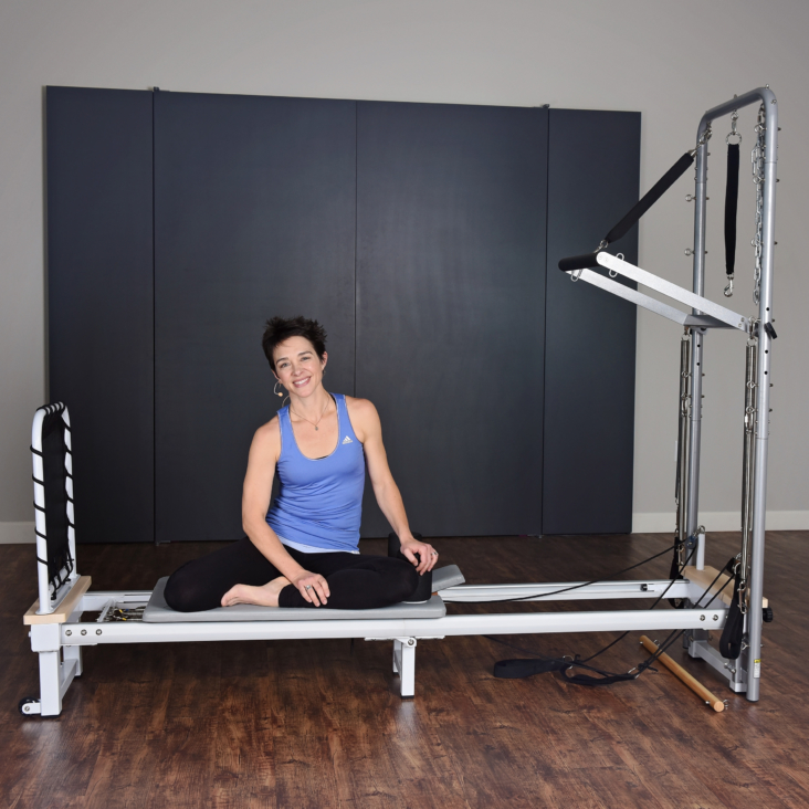Woman seat on AeroPilates Cadillac Reformer Combo